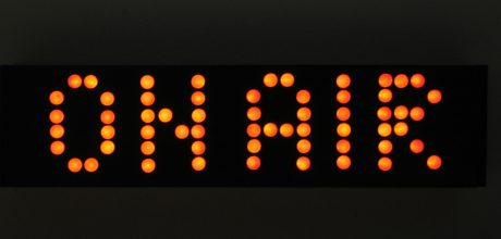 """On air"" spelled out on black background in orange lights"""